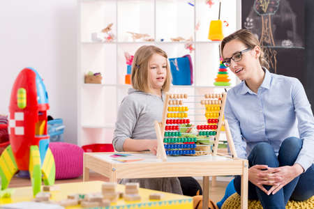 Foto de Little girl learning to count with her teacher in colorful playroom - Imagen libre de derechos