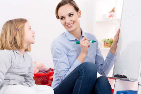 Foto de Therapist working with little girl with ADHD and reading problems - Imagen libre de derechos