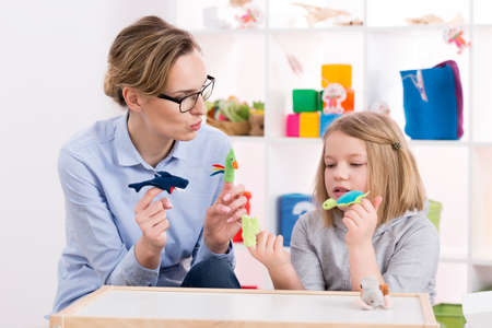 Photo pour Female teacher using colorful toys during play therapy with child - image libre de droit