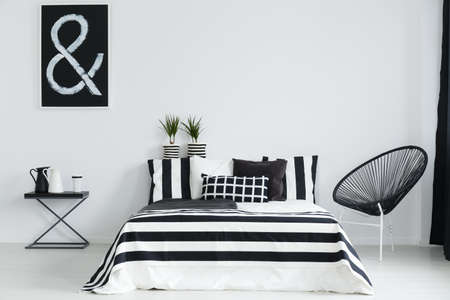 Photo pour Black and white bedroom with modern chair and night table - image libre de droit