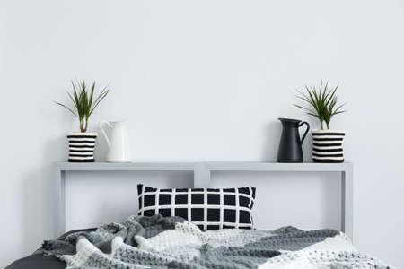 Foto de Double bed, grey blanket, checked cushion and decorative plants - Imagen libre de derechos