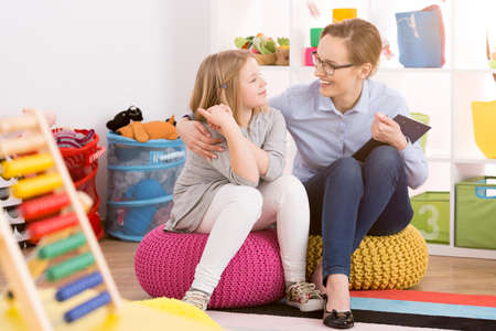 Foto de Young speech therapist working with child in colorful educational playroom - Imagen libre de derechos