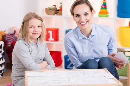 Foto de Female special educator and child patient during therapy using pictures - Imagen libre de derechos
