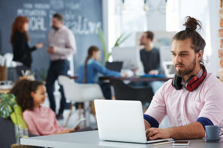 Photo for Young confident man working on startup using laptop in co-creative studio - Royalty Free Image