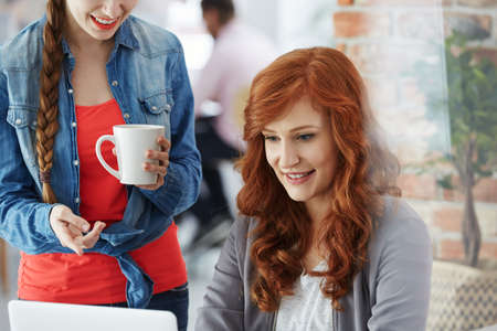 Photo for Attractive happy woman talking with coworker using laptop during coffee break - Royalty Free Image