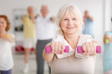 Foto de Senior woman exercising with pink dumbbells during classes - Imagen libre de derechos