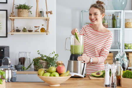 Foto de Happy woman preparing healthy green smoothie in her kitchen - Imagen libre de derechos