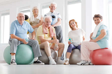 Photo pour Senior fitness team resting after workout on a gym - image libre de droit
