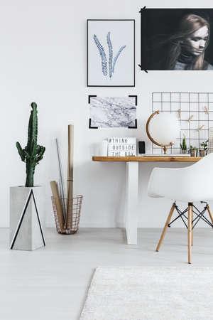 Photo pour Stylish white room interior with desk, chair and cactus - image libre de droit