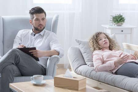 Foto de Handsome psychotherapist listening to sad young woman - Imagen libre de derechos