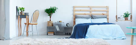 Photo pour Stylish designed blue bedroom with plants and wooden decoration - image libre de droit