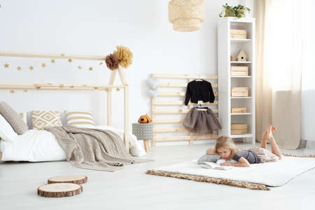 Photo pour Girl playing in white spacious dreamy bedroom in scandinavian style - image libre de droit