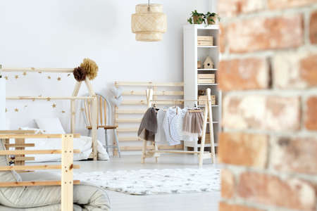 Photo pour Rustic brick wall in white and wooden scandinavian girl's room - image libre de droit