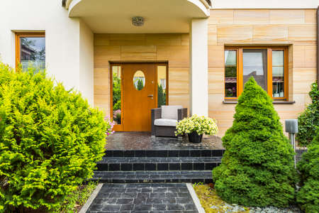 Photo pour Stylish front entrance to the modern family house with spruces next to cobblestoned pathway - image libre de droit