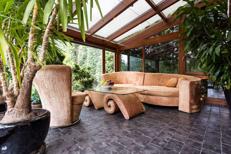 Foto de Stylish orangery with potted plants, glazed roof and unique velvet furniture - Imagen libre de derechos