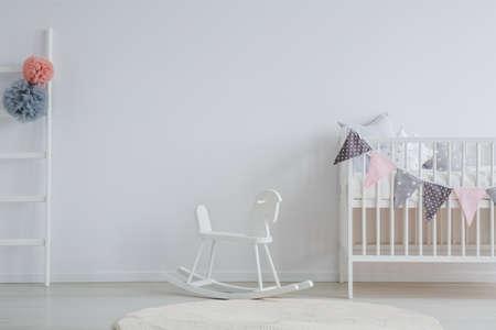 Photo pour Stylish baby room with white vintage rocking horse - image libre de droit