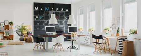 Foto de Black and white modern office with calendar on a blackboard - Imagen libre de derechos