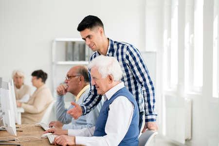 Photo pour Young handsome man checking senior's progress on IT task - image libre de droit