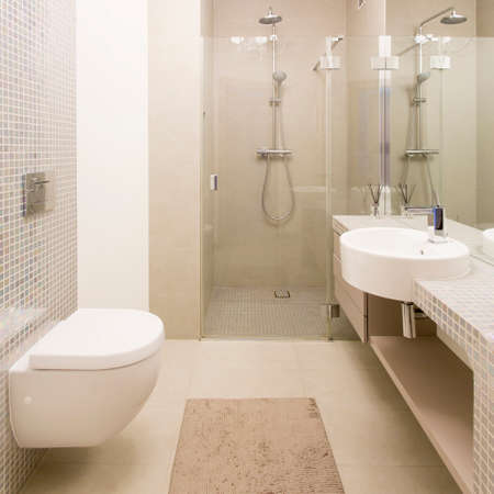 Photo for Spacious light bathroom with glass shower cabin, toilet and basin - Royalty Free Image