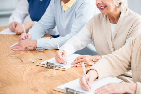 Photo for Older happy people writing a test during IT lecture - Royalty Free Image