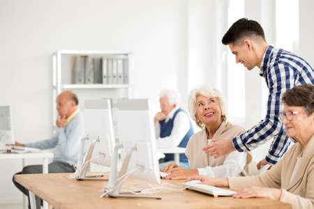 Foto de Young tutor explaining an IT task to senior lady - Imagen libre de derechos