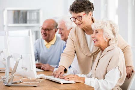 Photo pour Senior lady helping her friend with computer issue - image libre de droit