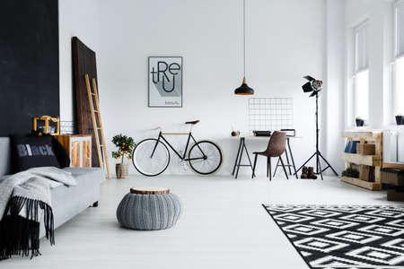 Photo pour Modern spacious studio apartment with sofa, bike and desk - image libre de droit