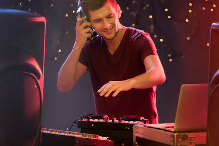 Photo for Happy handsome DJ playing in the club - Royalty Free Image