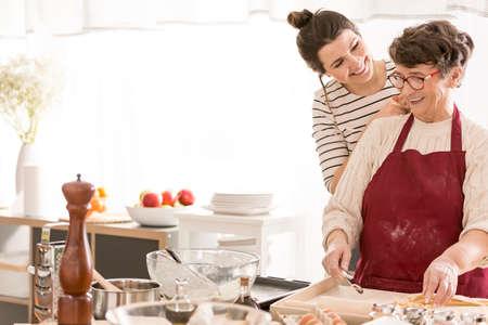 Foto de Granddaughter cooking with her happy grandma, having fun together - Imagen libre de derechos
