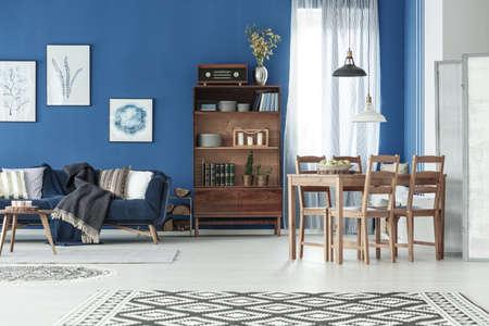 Foto de Stylish classic apartment with wooden dining table and vintage sofa - Imagen libre de derechos