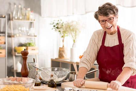 Foto de Happy senior woman rolling dough for pizza - Imagen libre de derechos