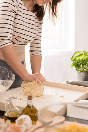 Photo pour Young woman preparing dough for fresh pasta, close up - image libre de droit