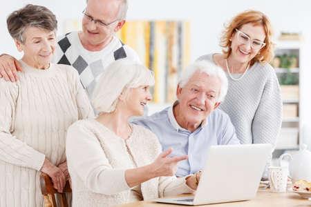 Photo pour Group of senior friends having video conference with friend - image libre de droit
