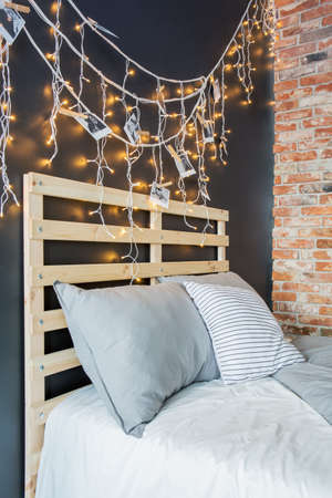 Photo for Creative pallet bed headboard with romantic fairy light decoration - Royalty Free Image