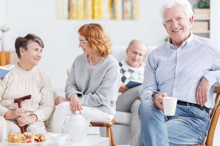 Foto de Elderly people drinking coffee in the afternoon in nursing home - Imagen libre de derechos