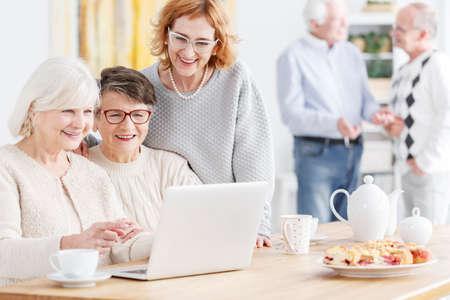 Photo pour Senior woman teaching her friends how to use laptop - image libre de droit