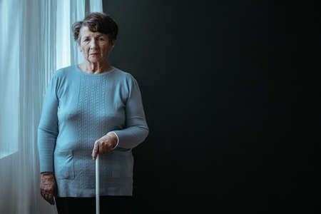 Photo pour Blind older lady standing with a white stick - image libre de droit