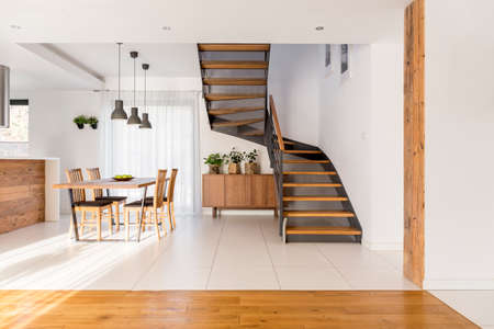 Foto de Open space with industrial half-landing stairs and wooden dining area - Imagen libre de derechos