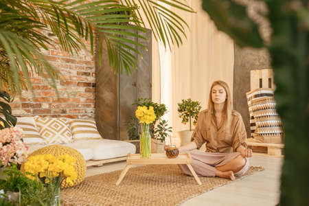Foto de Young woman relaxing in cozy loft with botanic decor - Imagen libre de derechos
