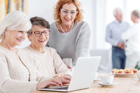 Photo for Three modern happy grandmothers using new technology laptop - Royalty Free Image