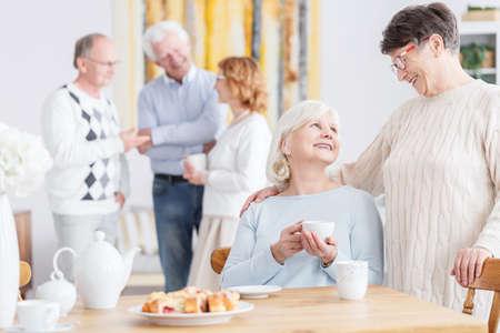 Foto de Elderly friends on a tea party at neighbor's home - Imagen libre de derechos