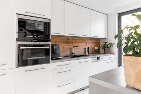 Photo pour Balanced kitchen with white cabinets grey worktop and natural accents - image libre de droit