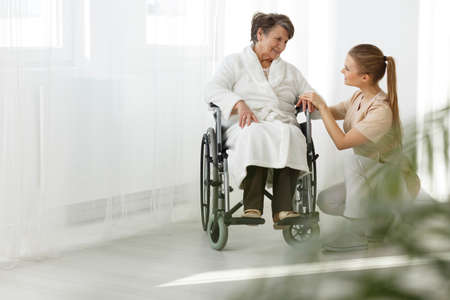 Foto de Senior lady in a wheelchair smiling at her nurse - Imagen libre de derechos
