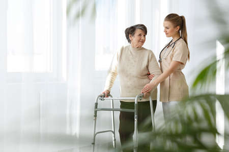 Photo pour Young nurse taking care of her senior lady patient - image libre de droit