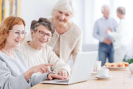 Photo pour Three older women using laptop to watch photos - image libre de droit