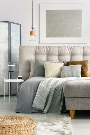 Photo pour Grey blanket and pillows on comfortable bed in spacious bedroom - image libre de droit