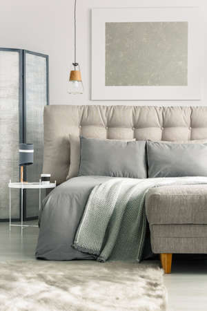 Photo for Grey cozy bedroom with comfortable bed and ottoman - Royalty Free Image