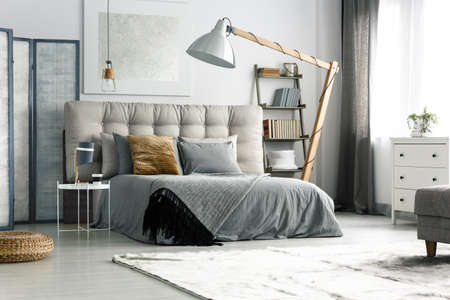 Foto de Grey screen by the bed in cozy spacious bedroom - Imagen libre de derechos