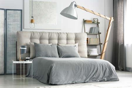 Foto de Big wooden lamp near comfortable bed with grey bedding - Imagen libre de derechos