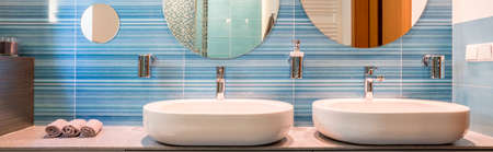 Photo pour Two sinks and mirrors in a blue bathroom - image libre de droit